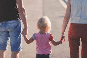 אמא ואבא וילדה מחזיקים ידיים